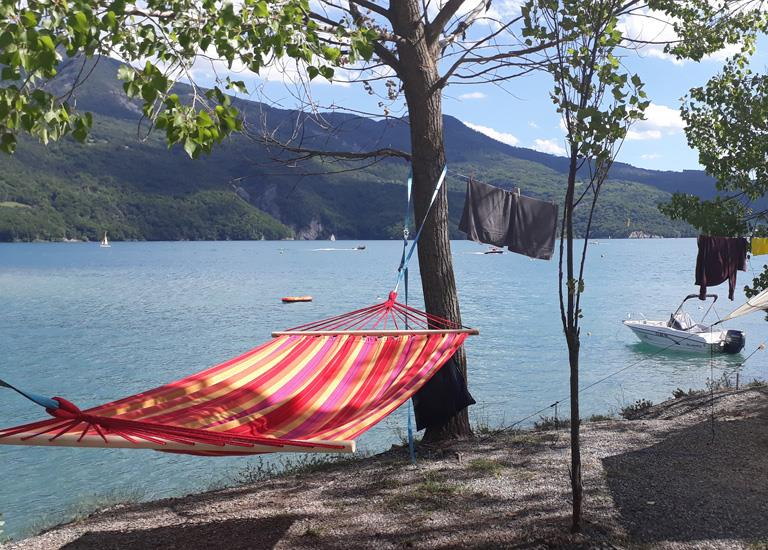 View of the hammock right by the side of the Serre-Ponçon Lake in the Camping Le Roustou, in the Hautes-Alpes