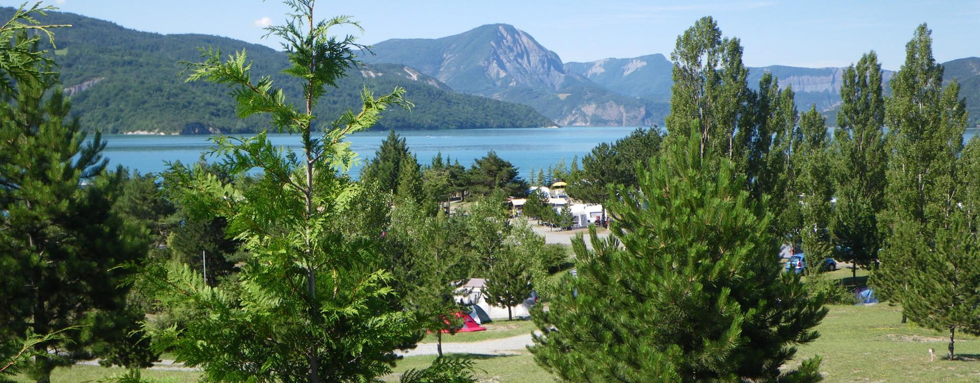 View of the camping spaces in Camping le Roustou on the edge of the Serre-Ponçon Lake